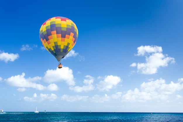 Bunter heißluftballon über blauem meer