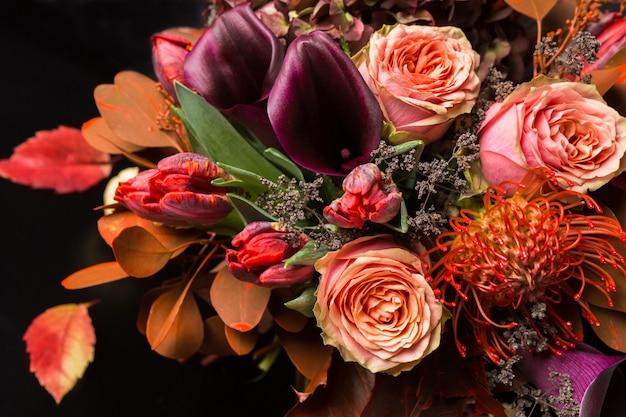Bunter herbststrauß. herbstzusammensetzung von rosen, tulpen, trockenen blättern und kräuternahaufnahme. blumengeschäft und floristen-designkonzept