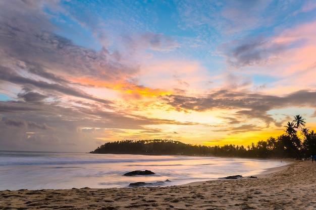 Bunter himmel bei sonnenuntergang auf tropischem strand der wüste