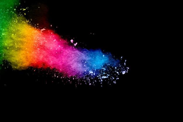 Bunter hintergrund der pastellpulver-explosion. regenbogenfarbstaubspritzer auf schwarzem hintergrund.