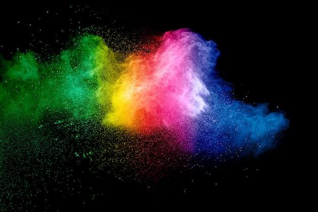 Bunter hintergrund der pastellpulverexplosion regenbogenfarbstaubspritzen auf schwarzem hintergrund.