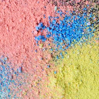 Bunter hintergrund des kreidepulvers. mehrfarbige staubpartikel splattered auf schwarzem hintergrund.