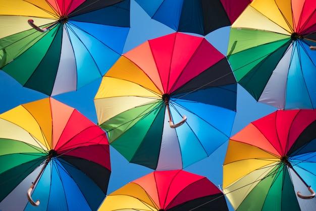 Bunter hintergrund von schönen regenschirmen gegen den blauen himmel