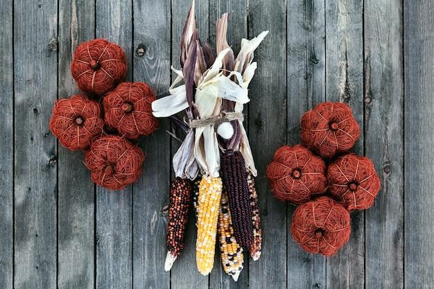 Bunter inder getrockneter mais auf holztisch mit dekorativen kürbisen
