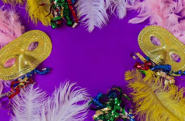 Bunter karnevalsrahmen mit masken und federn und lila hintergrund