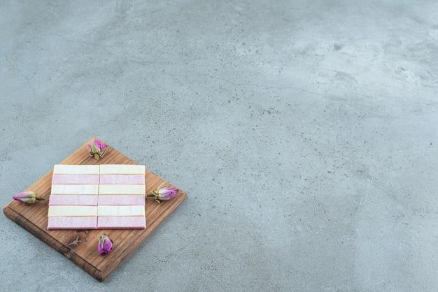 Bunter kaugummi mit getrockneten rosen auf holzbrett.