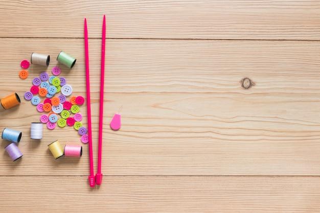 Bunter knopf und spule mit rosa stricknadeln auf hölzernem hintergrund