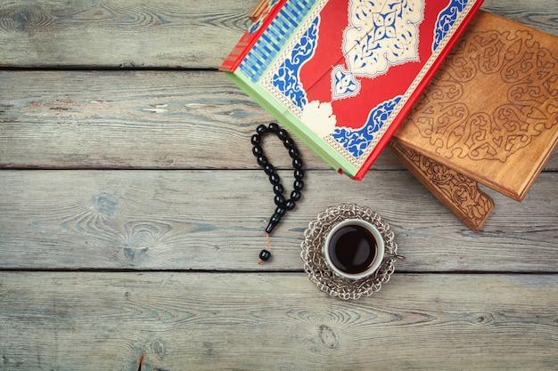 Bunter koran mit rosenbeet auf dem hölzernen hintergrund. heilige schrift für muslime für ramadan-konzept