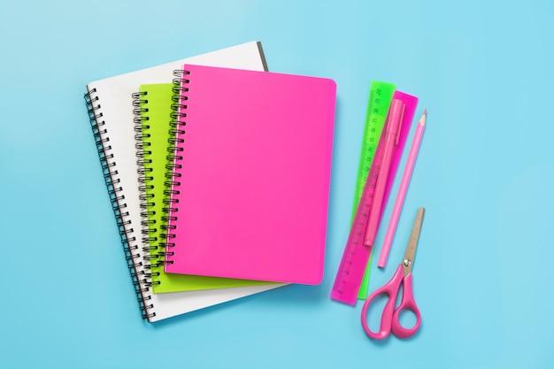 Bunter mädchenhafter schulbedarf, notizbücher und stifte auf schlagkräftigem blau. draufsicht, flach zu legen. kopieren sie platz.