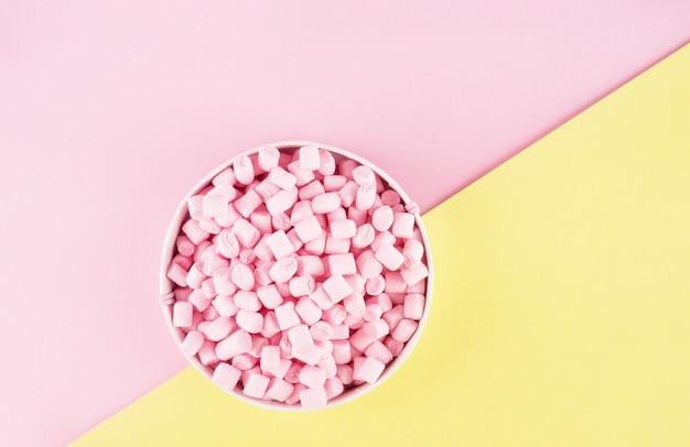 Bunter marshmallow auf rosa und gelber papieroberfläche