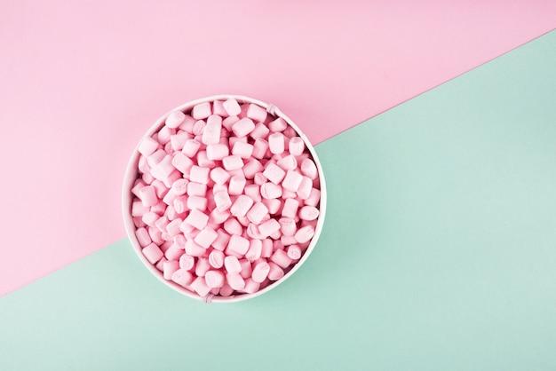 Bunter marshmallow auf rosa und mintfarbener papieroberfläche