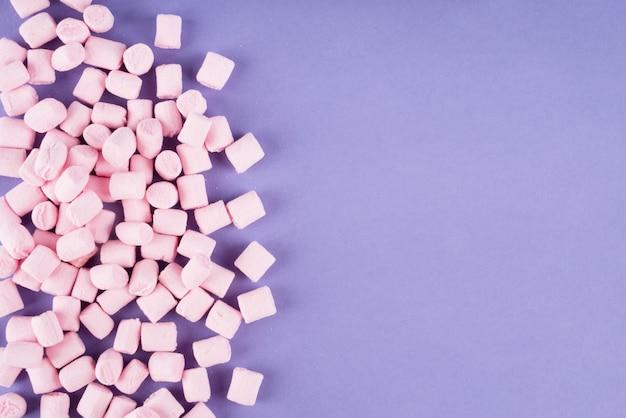 Bunter marshmallow auf violetter papieroberfläche