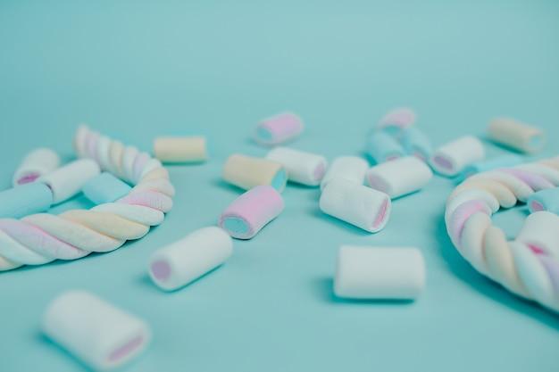 Bunter marshmallow. viele süßigkeiten auf dem tisch. gedrehter marshmallow mit süßigkeiten herum.
