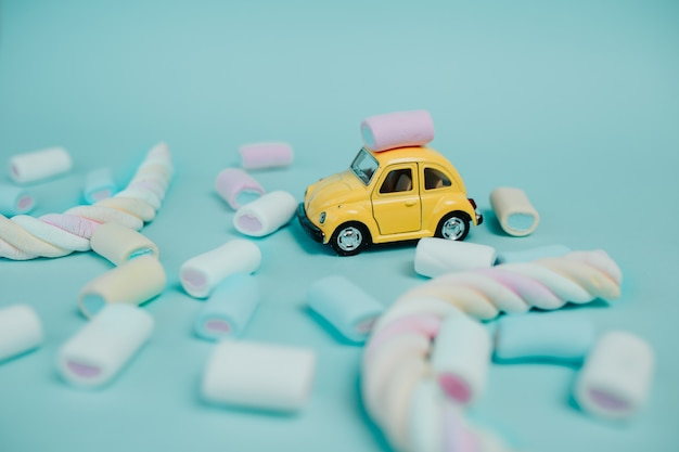 Bunter marshmallow. viele süßigkeiten auf dem tisch. gelbes spielzeugauto mit verdrehtem marshmallow und süßigkeiten herum.