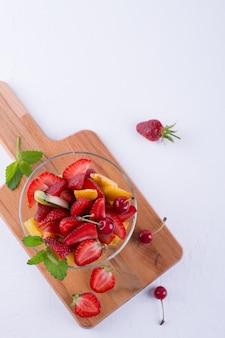 Bunter obstsalat in der glasschale. erdbeeren, kiwis und aprikosen draufsicht