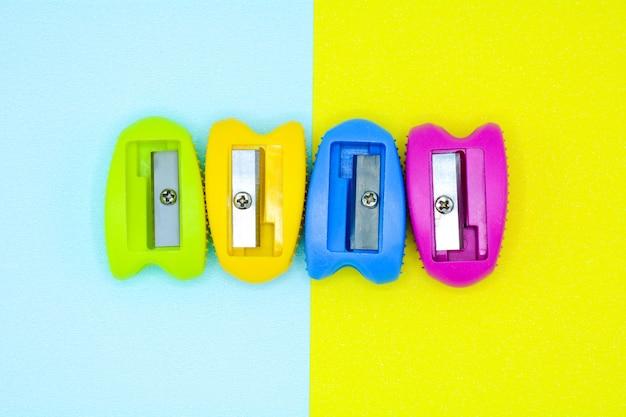 Bunter plastikbleistiftspitzer auf blauem und gelbem hintergrund