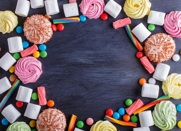 Bunter rahmen von mehrfarbigen süßigkeiten auf schwarzem hölzernem hintergrund.