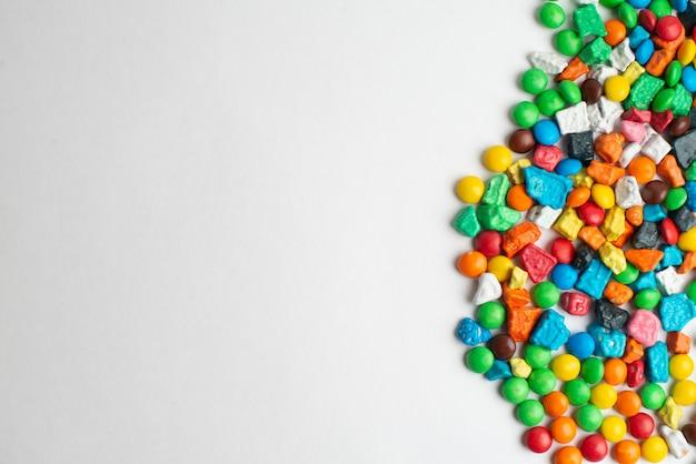 Bunter rahmen von mehrfarbigen süßigkeiten auf weißem hintergrund