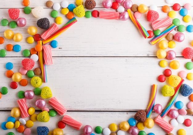 Bunter rahmen von mehrfarbigen süßigkeiten auf weißem hölzernem.