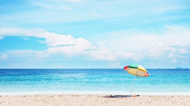 Bunter regenschirm auf sand über landschaft des blauen himmels und des meeres.