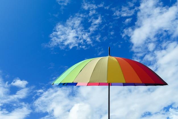 Bunter regenschirm mehrfarbig auf einem blauen himmelwolkenhintergrund