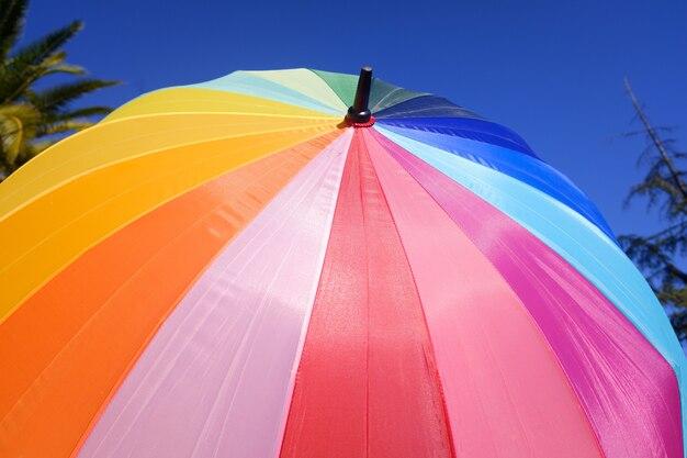 Bunter regenschirm schützt vor der sonne einen sommertag, wand des blauen himmels.