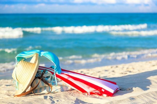 Bunter roter und weißer regenschirm mit strohhut, strandtasche und blauem bikini-bh-badeanzug gegen den ozeanstrand mit schönem blauem himmel und wolken