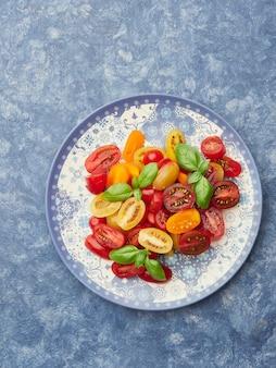 Bunter salat aus roten und gelben kirschtomaten mit basilikumblättern auf blauem teller und blauer oberfläche
