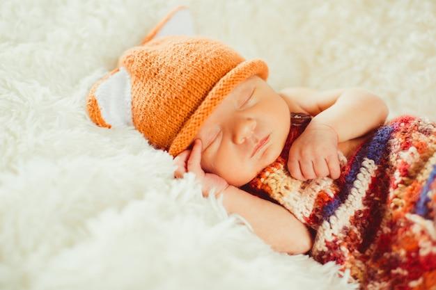 Bunter schal bedeckt das kleine baby, das auf dem flaumigen kissen schläft