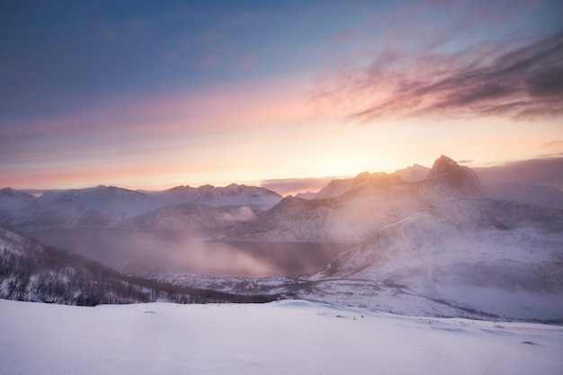 Bunter sonnenaufgang auf schneebedecktem berg