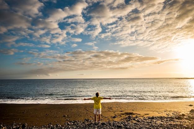 Bunter sonnenuntergang am strand und junger mann, der steht und die schönheit der natur und des ozeans genießt