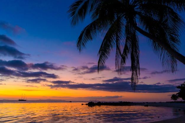 Bunter sonnenuntergang auf dem ozean. sonnenuntergangstreffen am strand. tropischer sonnenuntergang mit palmen