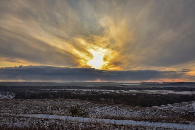 Bunter sonnenuntergang im feld, wintersonnenuntergang, orange heller sonnenuntergang im winterfeld, bunter himmel
