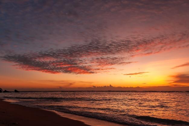 Bunter sonnenuntergang mit den farben blau, flieder, gelb, rot und orange, die den himmel und das meer malen.