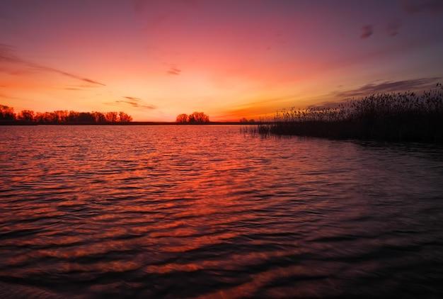 Bunter sonnenuntergang über meer. roter und oranger himmel. schnelle wellen