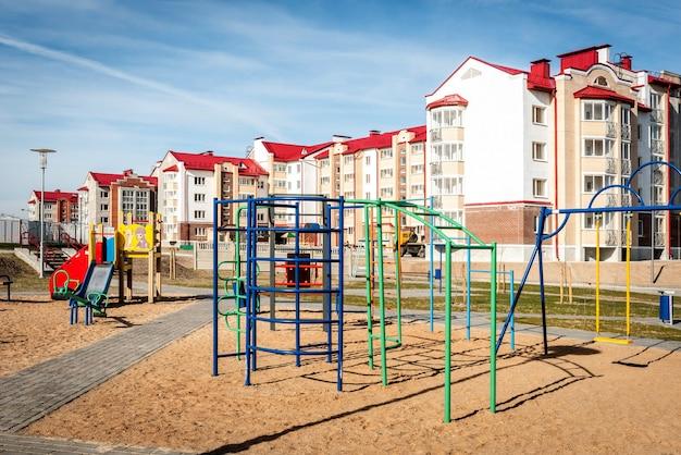 Bunter spielplatz für aktivitäten im sand in der nähe von mehrfamilienhäusern.