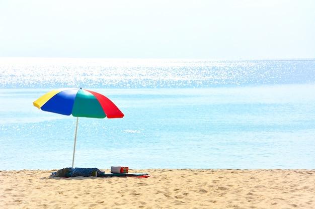 Bunter strandschirm mit einem kissen und einem kleinen kissen auf verlassenem strand an einem sonnigen tag