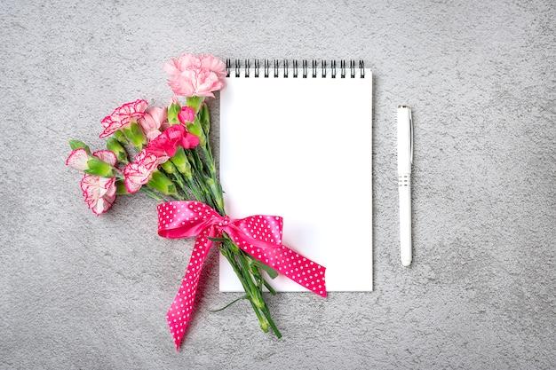 Bunter strauß der verschiedenen rosa nelkenblumen, weißes notizbuch, stift auf auf grauem beton