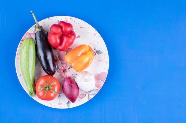 Bunter teller mit frischem reifem gemüse auf blauem tisch.