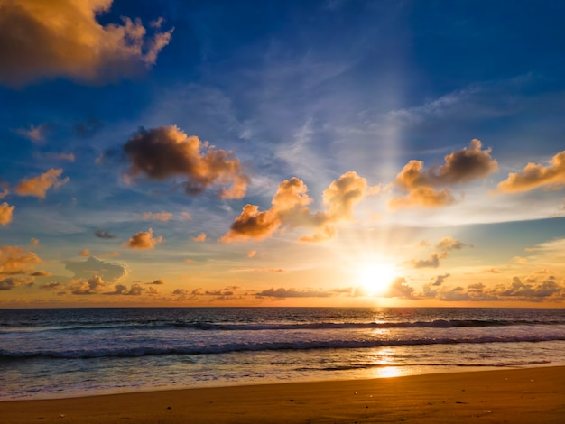 Bunter tropischer strandsonnenuntergang mit gelbem, blauem himmel und sonnenstrahl. sonnenuntergang über meer am strand von phuket, thailand.