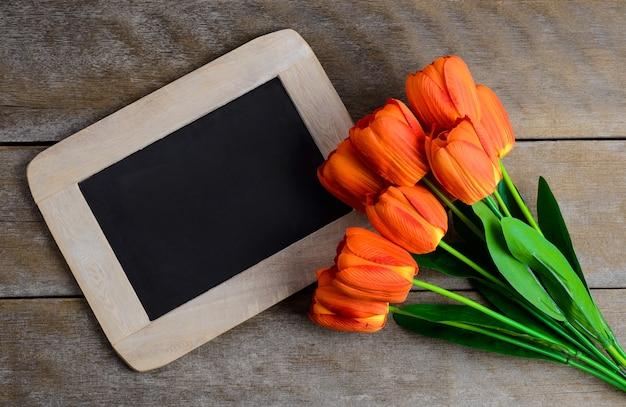 Bunter tulpenblumenstrauß und -tafel auf hölzernem hintergrund