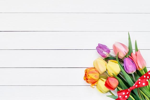 Bunter tulpenblumenstrauß verziert mit band auf weißem hölzernem hintergrund