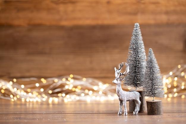 Bunter weihnachtsbaum auf hölzernem, bokeh hintergrund. weihnachtsfeiertagsfeierkonzept. grußkarte.