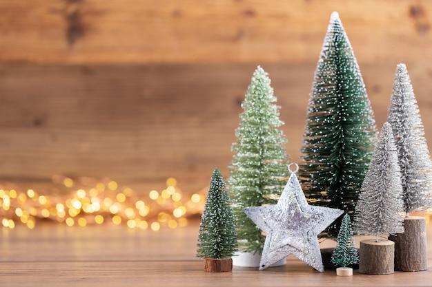 Bunter weihnachtsbaum auf holz-, bokeh-hintergrund. weihnachtsfeiertagsfeierkonzept. grußkarte.