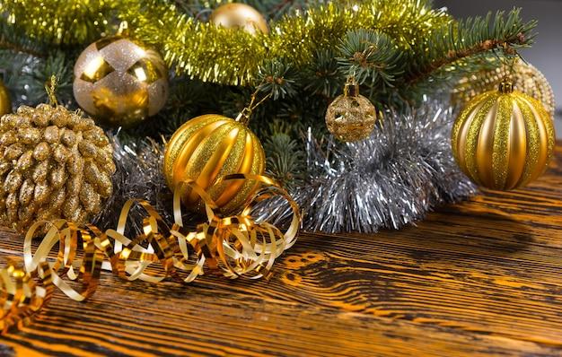 Bunter weihnachtshintergrund mit goldenen kugeln und lametta, die auf kiefernlaub über einem rustikalen holzhintergrund mit exemplar angeordnet sind