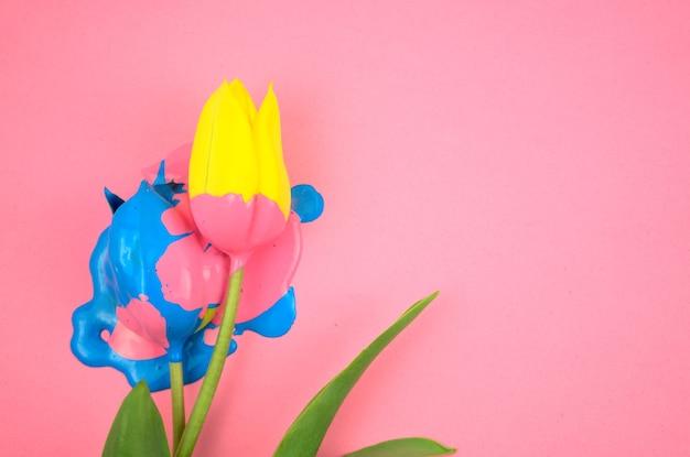 Buntes acryl und gelbe blumentulpe flach auf klarem rosa hintergrund.