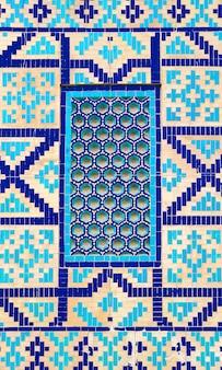 Buntes altes traditionelles usbekmuster auf dem keramikziegel auf der wand der moschee, abstrakter hintergrund