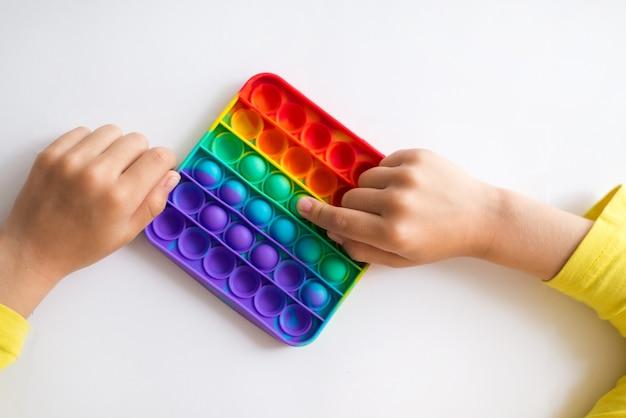 Buntes anti-stress-sinnesspielzeug zappeln, drücken sie es in kinderhände