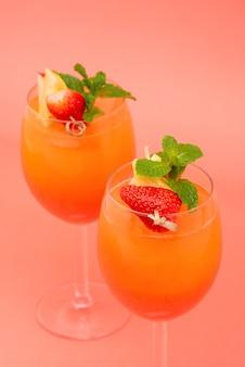 Buntes auffrischungserdbeerorangen-sonnenaufgangcocktail trinkt in den gläsern