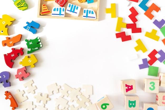 Buntes babykinderspielzeug auf weißem hintergrund. rahmen aus der entwicklung bunter blöcke, autos und flugzeuge, rätsel. draufsicht. flach liegen. kopieren sie platz für text